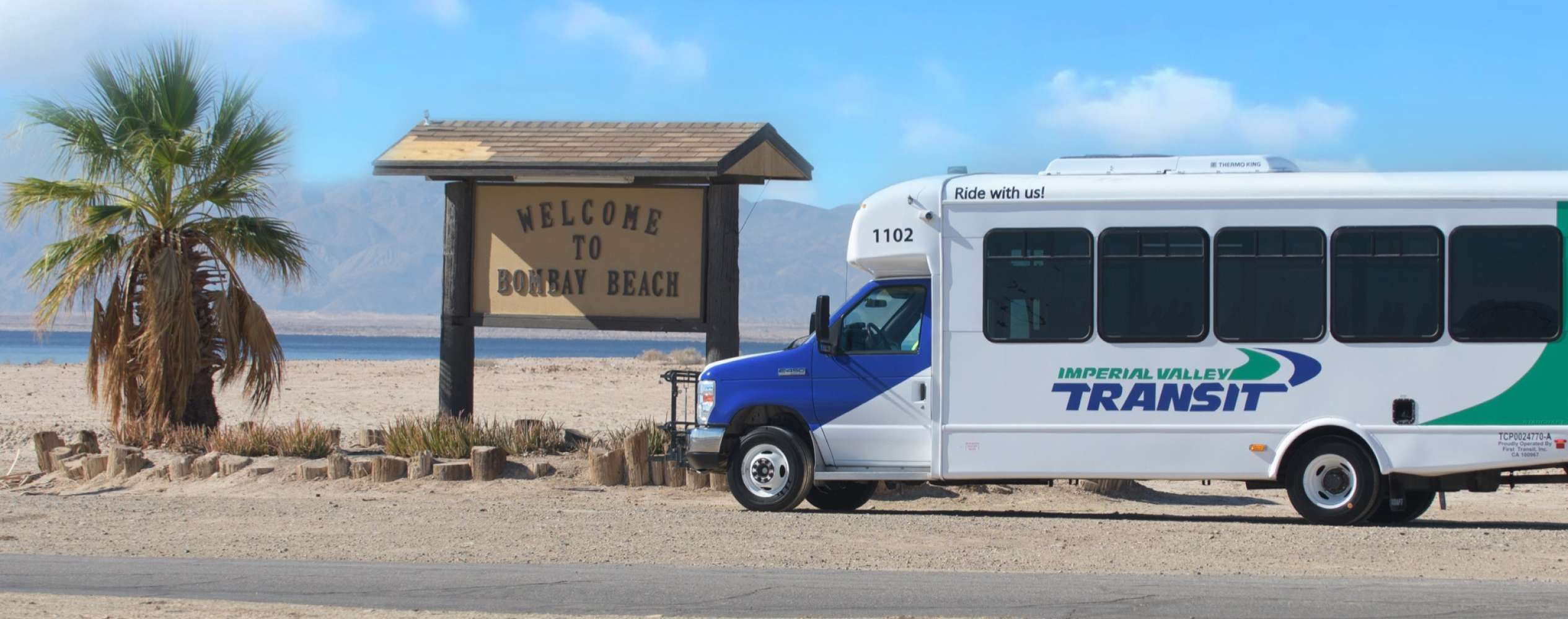 Bus parked next to 'Welcome to Bombay Beach' sign
